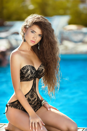slim girl: Beautiful bikini girl model with long healthy hair tanned and relaxing by the swimming pool, summer vacation, beauty fashion outdoor portrait.