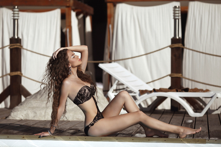 beach model: Bikini model. Beautiful sexy brunette girl model with long wavy hair, sunburn on the beach wearing in black fashion swimsuit. Vacation. Tanned woman.