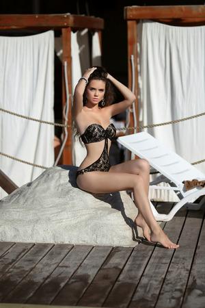 sitting pretty: Bikini model. Beautiful sexy brunette girl model with long wavy hair, sunburn on the beach wearing in black fashion swimsuit. Vacation. Tanned woman.