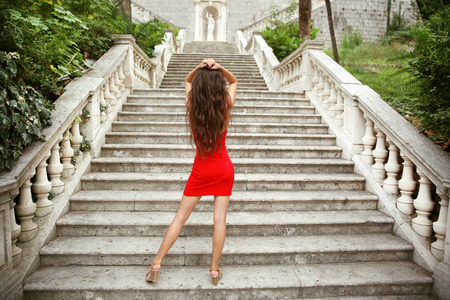 Beautiful young brunette girl model in red dress posing on staircase in Birth of our Lady Church, Montenegro