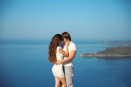 pareja apasionada: Pareja apasionada bes�ndose sobre el mar y el cielo azul de fondo. Placer. d�as de fiesta, vacaciones, el amor y el concepto de la felicidad.