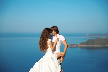 passion couple: Bride and Groom outdoor portrait. couple having passion over blue sky background. Enjoyment. holidays, vacation, love and happiness concept. Montenegro. Stock Photo