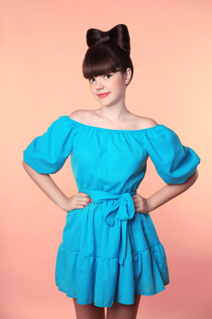beautiful teen girl: Hairstyle. Beautiful smiling girl with bow hair posing in blue dress isolated on studio background.