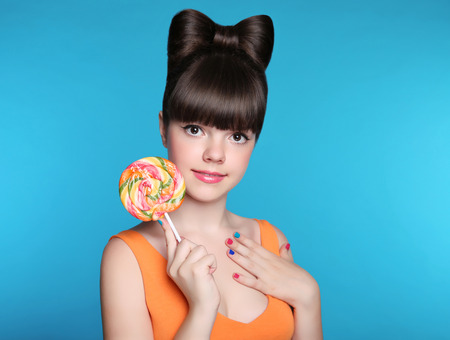 beautiful background: Beauty smiling teen girl Eating colourful lollipop. Stock Photo