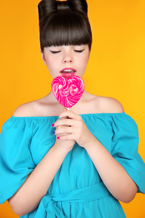 yellow heart: Lollypop candy. Beautiful teen girl eating colourful Heart lolli pop.