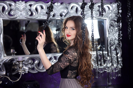 elegance: Beautiful smiling young girl with long hairstyle curly hair and red lips Stock Photo