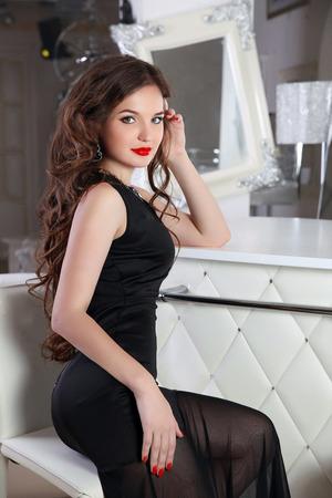 belle brune: Belle brune modèle femme sexy en robe noire élégante assis sur une chaise par comptoir en intérieur blanc et moderne.