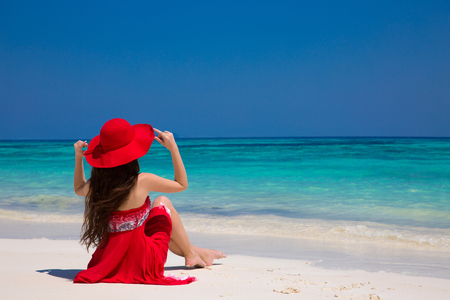 red dress: Happy woman enjoying beach relaxing joyful on white sand in summer by tropical blue water. Bliss freedom beach concept. Good life. Vacation. Stock Photo
