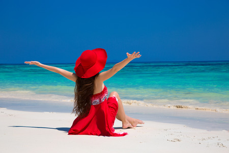 bliss: Beautiful woman in hat enjoying and relaxing on beach with white sand in summer by tropical blue water. Bliss freedom beach concept. Good life. Vacation.