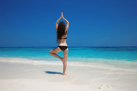 tree position: Young Woman meditating in tree yoga position on the exotic beach. Zen, meditation, peace. Balance. Bliss freedom concept.