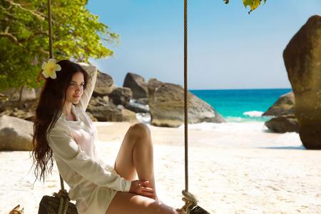 sea beach: Beautiful young woman on a swing resting on exotic beach with white sand by sea blue water, seashore. Wellness. Rock. Lifestyle.