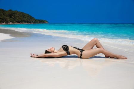 black bikini: Beautiful sexy woman in black bikini lying on exotic tropical beach beside blue water by seashore. Summer vacation. Sun tanning girl on white sand. Stock Photo