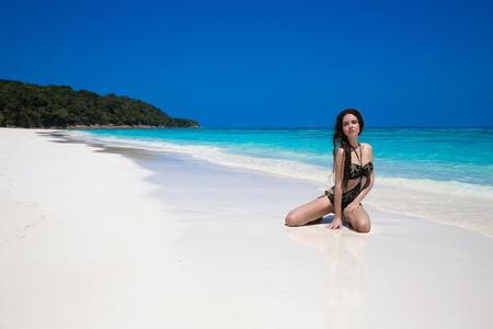 sun tanning: Beautiful sexy bikini model woman posing relaxing on exotic tropical beach beside blue water by seashore. Summer vacation. Sun tanning girl on white sand.