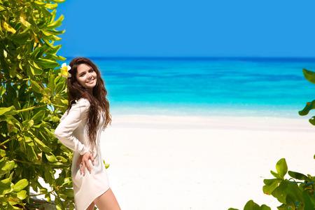 Free Happy lächelnde Frau, die Natur genießen am tropischen Strand. Schönheit Mädchen im Freien. Freiheit Konzept. Schönheit Mädchen über Himmel und blaues Meer. Wellness. Lebensstil. Vergnügen.