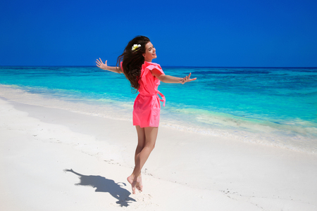 paradise beach: Fitness. Beautiful happy woman jumping on exotic sea, brunette smiling girl in red dress enjoying on tropical beach. Enjoyment. Lifestyle. Freedom. Good life. Travel. Stock Photo