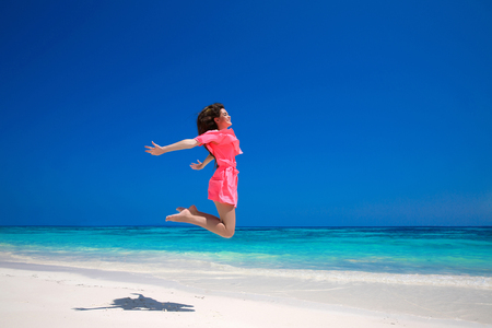 red dress: Summer enjoyment. Happy young woman jumping on the sea, brunette smiling girl in red dress running on tropical beach. Enjoyment. Lifestyle. Freedom. Good life. Travel. Stock Photo
