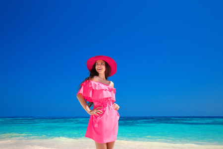 Fashion Summer Girl portrait. Happy woman enjoying on the sea, brunette smiling girl in red dress and elegant hat posing over blue sky on tropical beach with white sand.