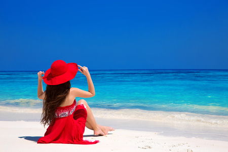 red white blue: Beauty fashion woman in red hat enjoying beach relaxing joyful on white sand in summer by tropical blue water. Bliss freedom beach concept. Good life. Vacation.