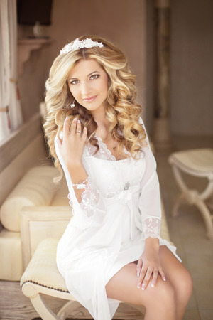 blonde woman: Beautiful smiling bride girl with makeup long wavy hair. Blond woman with curly hairstyle. Stock Photo