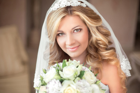 bridal salon: Wedding portrait Beautiful bride girl with long wavy hair and makeup. Happy smiling woman with bouquet of roses. Stock Photo