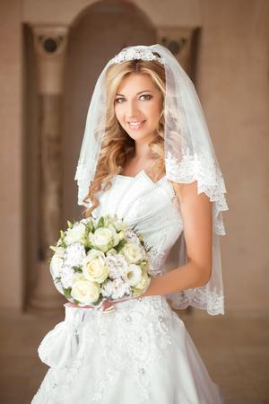 ウェディング ドレスと白いベールのモダンな家庭背景にポーズでバラの花束を持つ美しい笑顔花嫁少女。