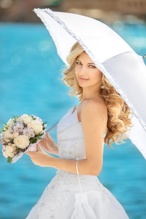 sunny day: Beautiful woman with white umbrella and roses bouquet of flowers, posing over seafront at sunny day. Stock Photo