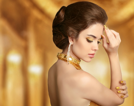 Beautiful fashion woman in gold, elegant lady in expensive pendant  jewelry close-up. Beauty Hairstyle. Reklamní fotografie