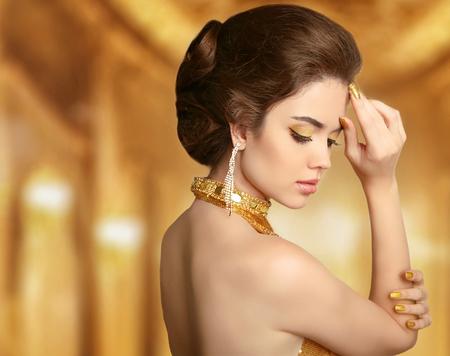 aretes: Mujer hermosa de la manera en oro, elegante dama en costosas joyas colgantes de primer plano. Belleza Peinado.
