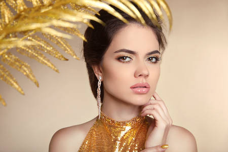 brown eyes: Golden luxury Jewelry. Manicured nail. Fashion art photo of young woman isolated on beige background. Stock Photo
