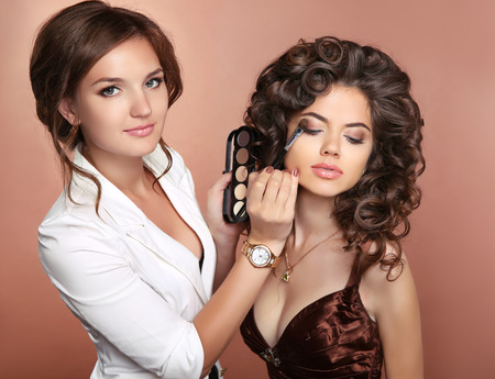 Curly hair. Beauty makeup. Professional artist woman applying make up sensual brunette girl model with red lips and shiny healthy hairstyle.