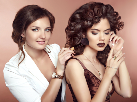 hair dresser: Hair. Beauty Makeup. Beautiful two Brunette smiling Girls. Make-up artist with brush. Hairstyle. Attractive young women posing at camera. Manicured nails. Jewelry.