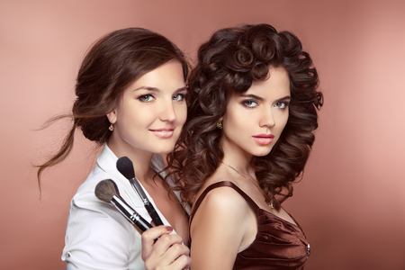Beauty women. Haistyle. Makeup Artist holding brush posing with fashion model. Beautiful two smiling Brunette Girls. Attractive young ladies looking at camera.