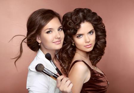 Capelli. Belle due sorridente bruna ragazze. Makeup artist con pennello. Acconciatura. Giovani donne attraenti che propongono alla macchina fotografica.