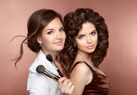 stylist: Hair. Beautiful two Brunette smiling Girls. Makeup artist with brush. Hairstyle. Attractive young women posing at camera. Stock Photo