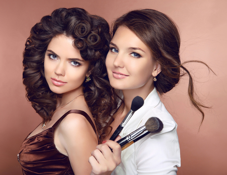 professional woman: Beautiful smiling girls. Makeup Beauty. Hairstyle. Professional artist with make-up brush and attractive brunette woman posing at camera isolated on studio background.