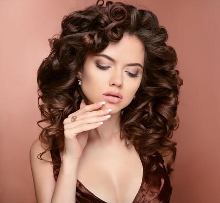 uñas largas: uñas cuidadas. Cabello. Modelo hermosa morena chica con el peinado brillante y sedoso y rizado y maquillaje. Marrón.