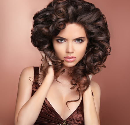 stare: Healthy hair. Stare. Beautiful young sexy woman with long curly hairstyle. Brunette with professional makeup.