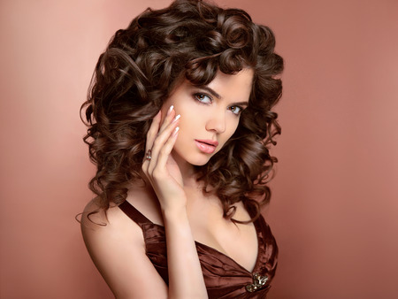 curly: Hairstyle. Beautiful young woman with long curly hair, beauty makeup and polish manicured nails. Brunette girl model with healthy shiny brown hairs. Stock Photo