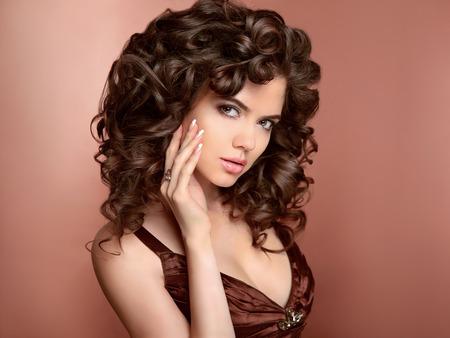 cabello rizado: Peinado. Hermosa mujer joven con el pelo largo y rizado, maquillaje de belleza y uñas pintadas de esmalte. Modelo de la chica morena con pelos marrones brillantes sanos.