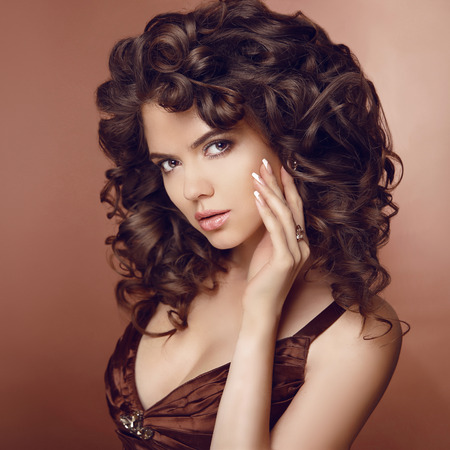 long hairs: Healthy hair. Beautiful young smiling woman with long curly hairs. Brunette girl model with professional makeup and Manicured nails. beige brown colour.