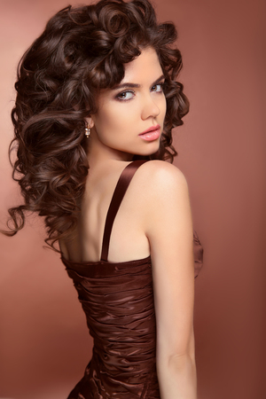 long hairs: Healthy hair. Beautiful brunette young  woman with long curly hairs. Elegant lady with professional makeup posing in dress.