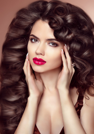 coloration: Healthy hair. Makeup. Beautiful brunette girl with long wavy hairstyle. Elegant lady with Red lips. Women beauty face. Studio portrait.