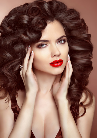 women face stare: Red lips. Makeup. Healthy hair. Beautiful brunette girl with long wavy hairstyle.  Elegant lady, beauty studio portrait. Skin care.
