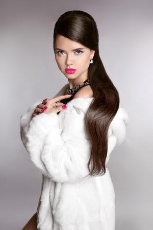 Beauty elegante Mädchen im weißen Luxus-Pelz-Mantel. Bilden. Frisur. Winter-Studio Portrait Frau mit langen gesund.