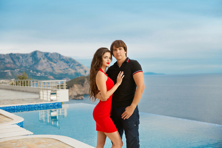 summer dress: Young fashionable couple. Vacation holidays background. Handsome man posing with Beautiful  woman in red dress. Stock Photo