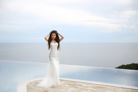 pageant: Brunette model in luxurious fashion white gown posing by infinity swimming pool over sea. outdoor portrait.