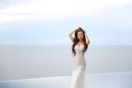 pageant: Beautiful Bride in wedding dress, outdoor portrait. Brunette elegant woman in luxurious fashion white gown posing over sea. Attractive girl with long blowing hair style. Stock Photo