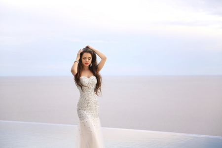 Beautiful fashion bride girl in beaded wedding dress. Summer holiday concept. Luxury resort woman in long gown posing by infinity swim pool over sunset sky with sea.