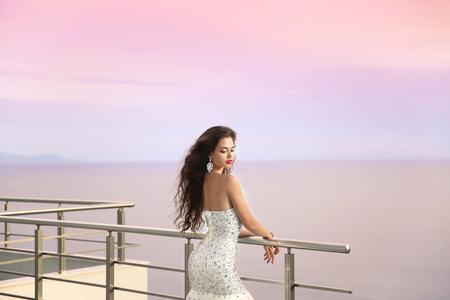 anochecer: Retrato de boda de la novia niña hermosa en vestido de lujo con cuentas. el concepto de moda vacaciones de verano. Mujer elegante que goza en el balcón que mira el cielo del atardecer sobre el mar.
