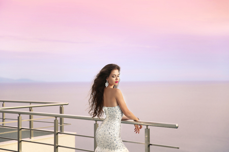 evening dress: Wedding portrait of Beautiful bride girl in beaded luxurious dress. Summer holiday fashion concept. Elegant woman enjoying on balcony looking sunset sky over sea.
